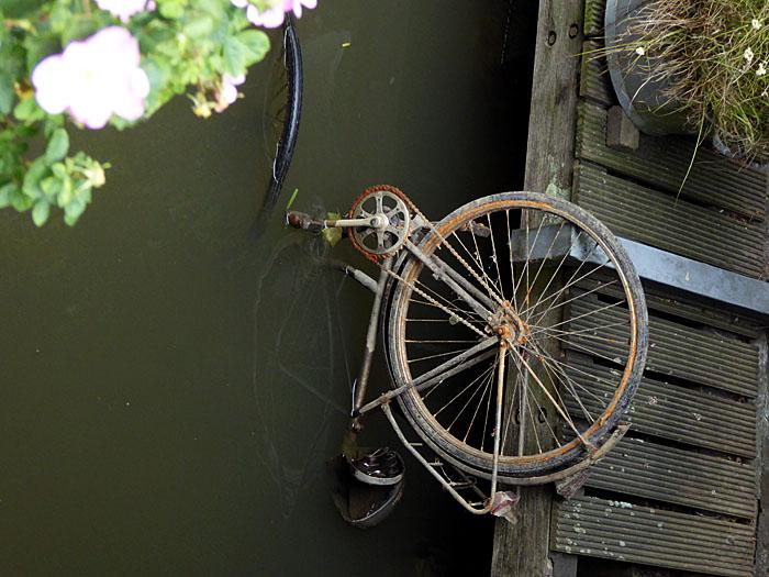 Foto van fiets half in het water