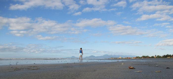 Foto van wandelaar op strand, wolkenlucht