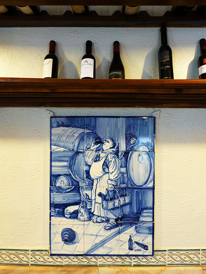 Foto van tegeltableau met dikke drinkende monnik