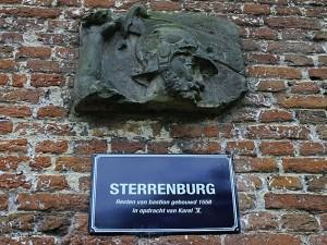 Foto van muur met reliefsteen met gehelmd hoofd en naambordje
