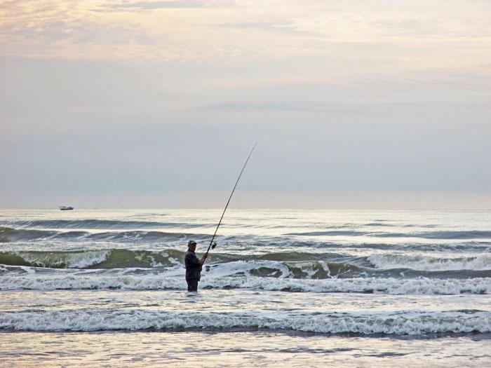 Foto van (zee)sportvisser in de golven