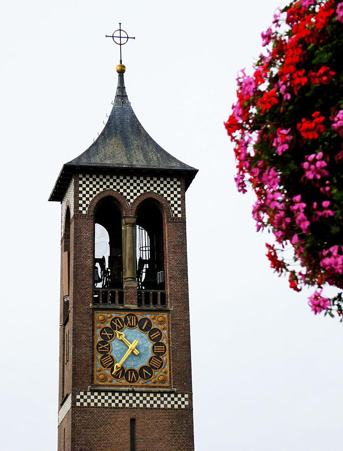 Foto van kerktoren en tuil bloemen