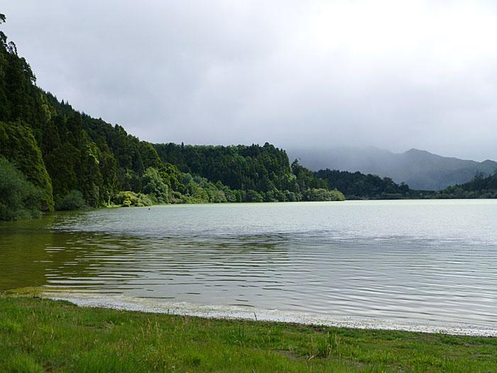 Foto van meer omringd door groene helling