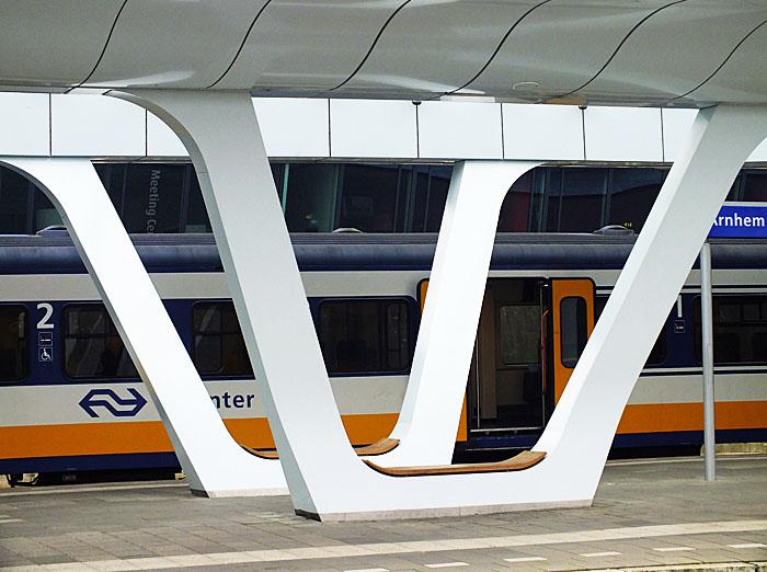 Foto van schuine, iets gebogen pilaren onder stationskap