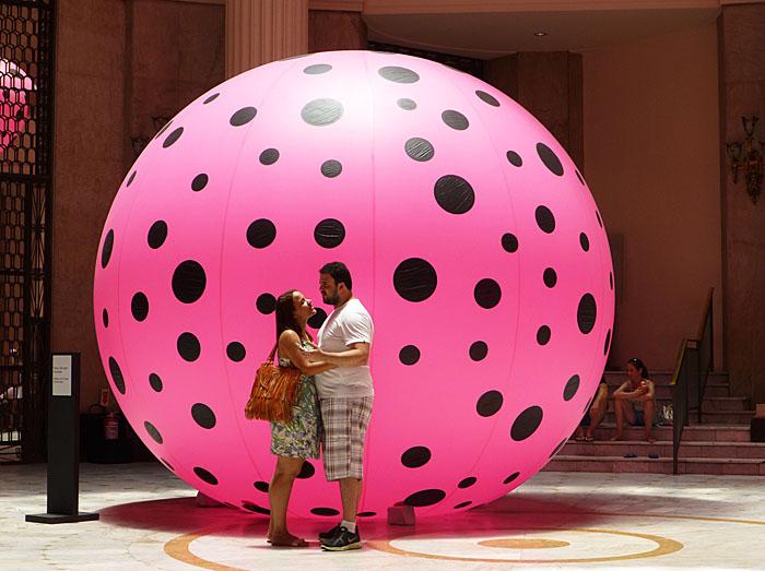 Foto van paartje voor roze bal met zwarte stippen