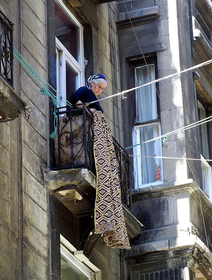 Foto van vrouw op balkon met kleed