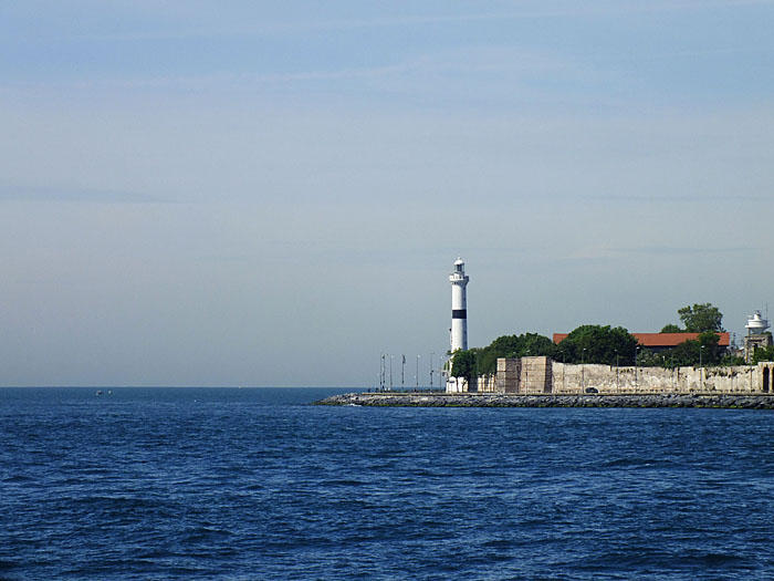 Foto van landtong met vuurtoren in blauwe zee