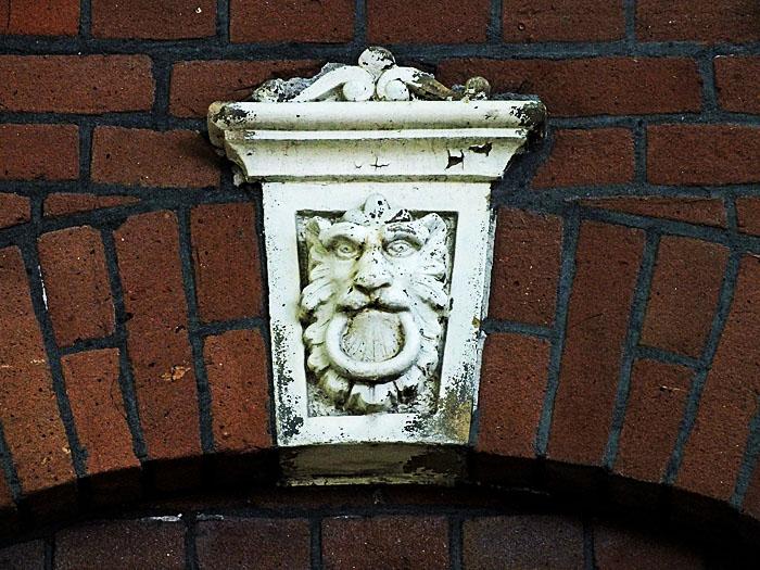 Foto van gevelsteen met leeuw met ring in de bek