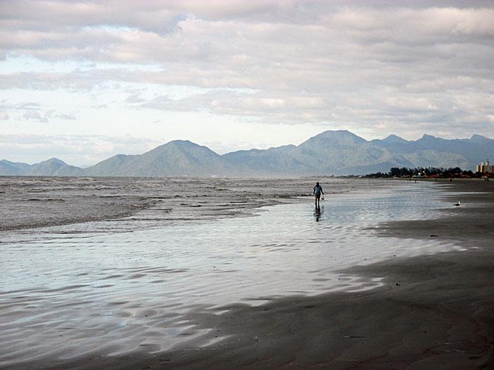 Foto van strand, bergen en wolken met eenzame wandelaar