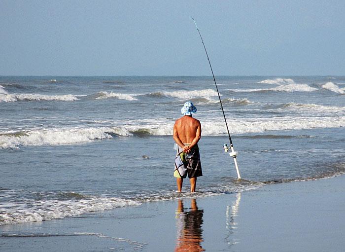 Foto van zeevisser turend naar zijn vislijn