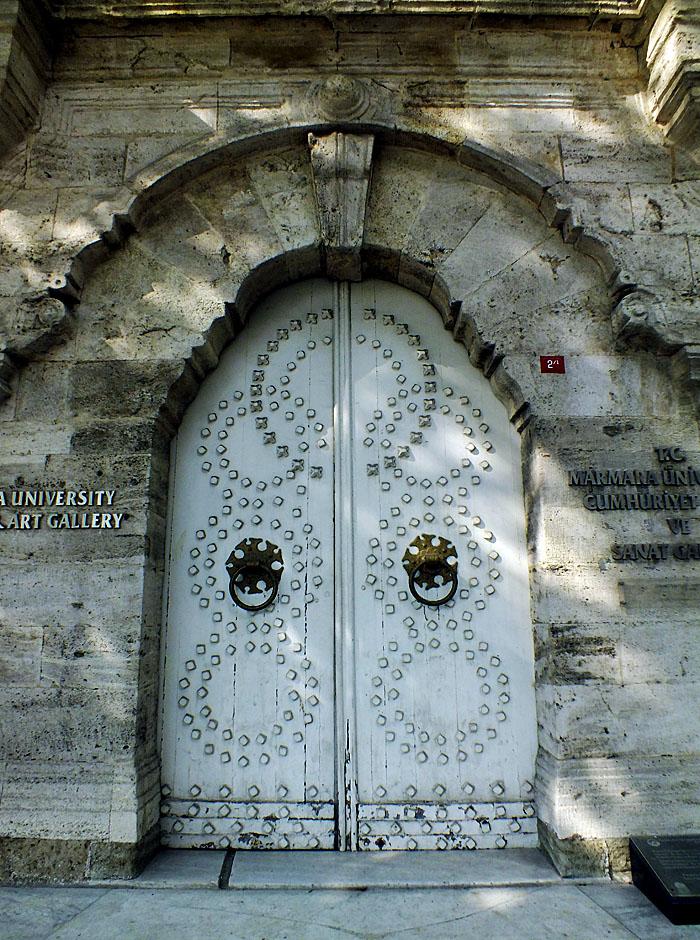 Foto van witte deur met metalen knoppen in cirkelvorm