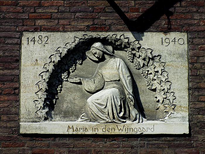 Foto van gevelsteen met gehurkte Maria