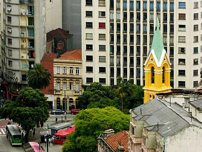 Foto van plein met kerk tusse hoge en lage gebouwen