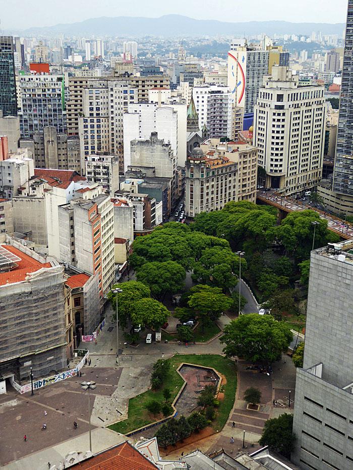 Foto van parkje tussen gebouwen, bergen op achtergrond