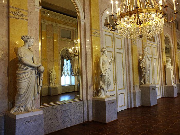 Foto van zaal met standbeelden en spiegels