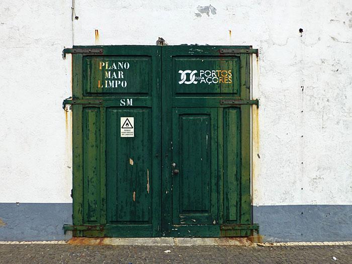 Foto van groene deuren in witte muur