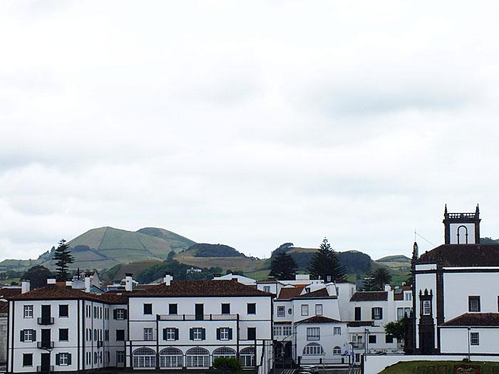 Foto van witte huizen voor groene heuvels