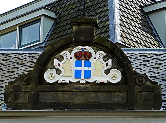 Foto van gevelsteen met wapenschild en kroon