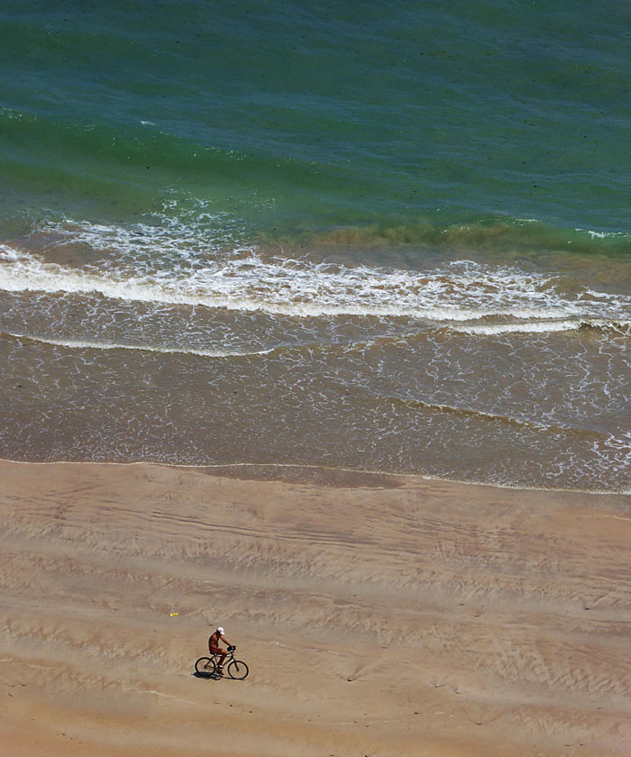 Foto van fietser op strand