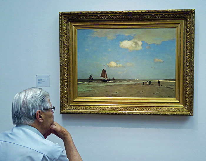 Foto van man die naar schilderij kijkt