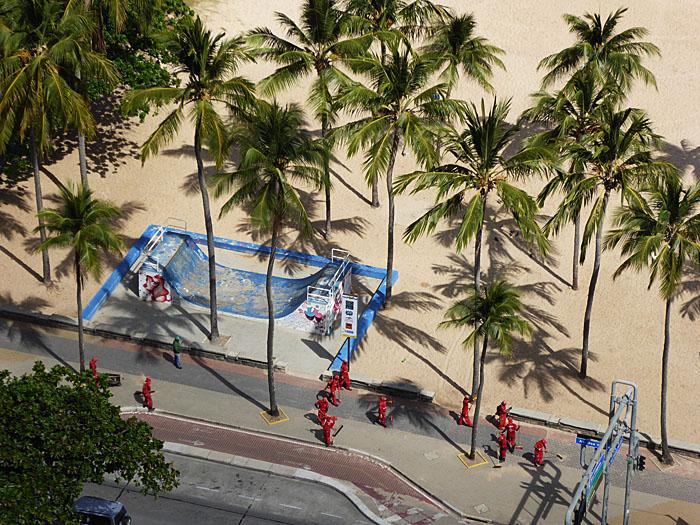 Foto van straatvegers tussen palmbomen