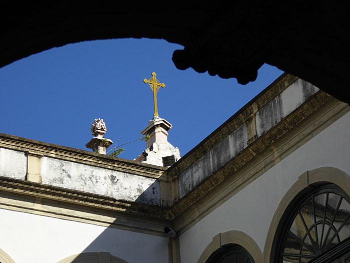 Foto van detail van kloostergang met kruis