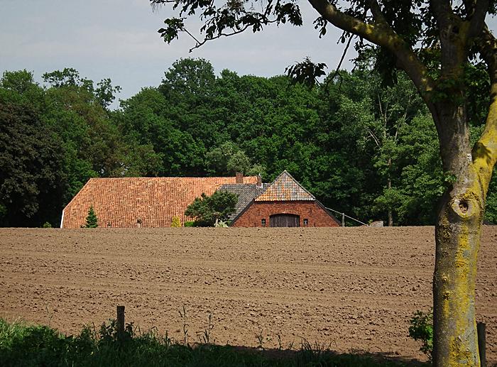 Foto van geploegde akker en boerderij
