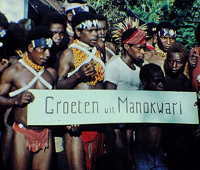 Foto van papua's met bord 'Groeten uit Manokwari'