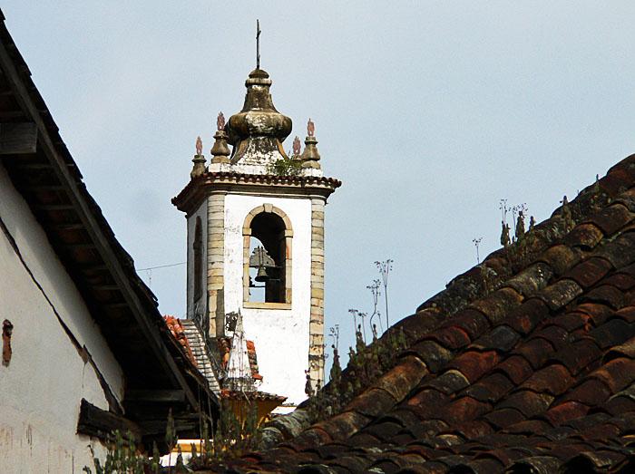 Foto van kerktoren tussen daken
