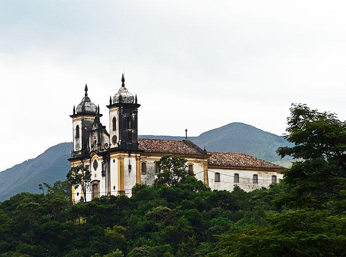 Foto van kerk op heuvel tussen groen