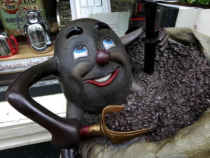 Foto van koffieboon als pop, die koffiebonen schept