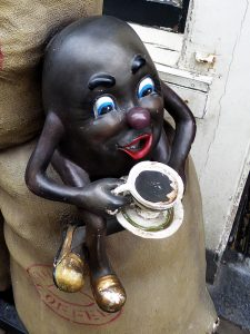 Foto van koffieboon als pop, die koffie drinkt
