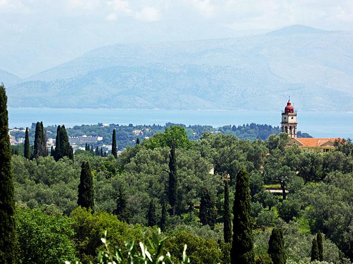Foto van uitzicht met cypressen en kerk