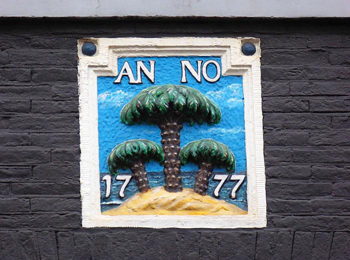 Foto van gevelsteen met palmbomen op zandheuvel