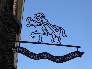 Foto van metalen 'uithangijzer' met heilige te paard en naam kerk