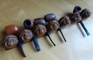 Foto van pijpenrek met houtsnijwerk (koppen)