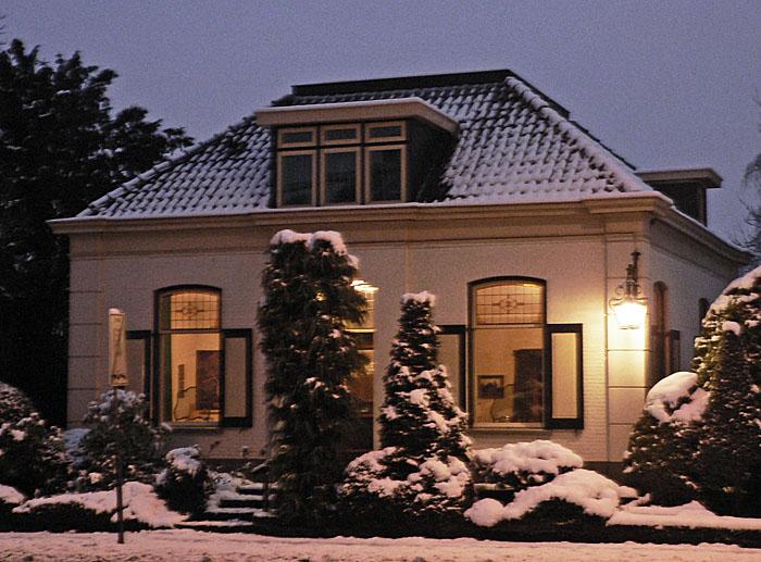 Foto van huis bij avond in sneeuw