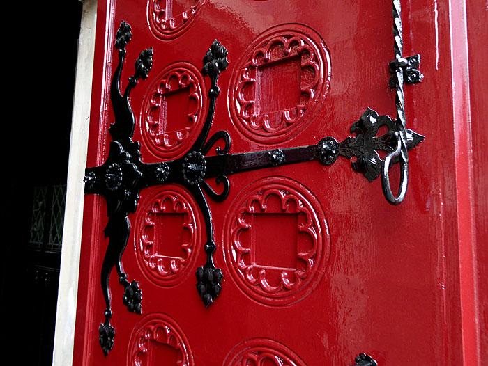 Foto van grote scharnier aan rode deur
