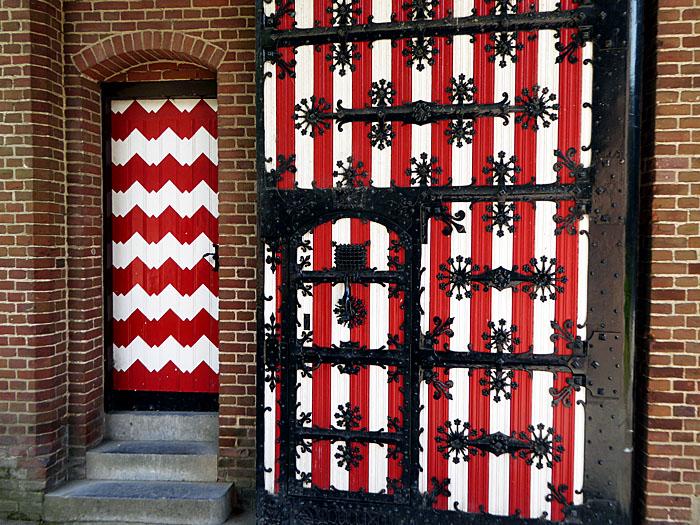 Foto van roodwitte deuren, een met zwart ijzerbeslag