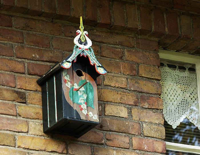 Foto van vogelhuisje aan muur
