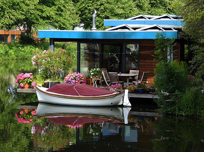 Foto van bootje bij woonboot met bloemen