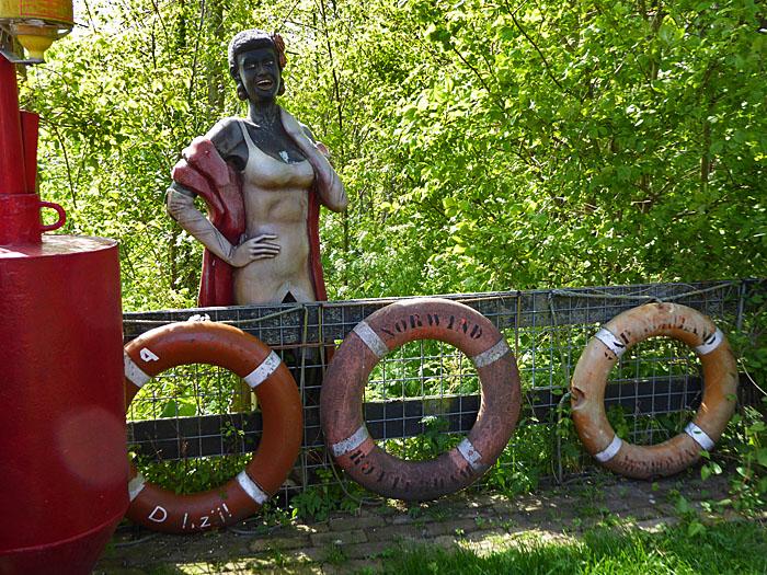 Foto van vrouwenbeeld achter hek met reddingsboeien