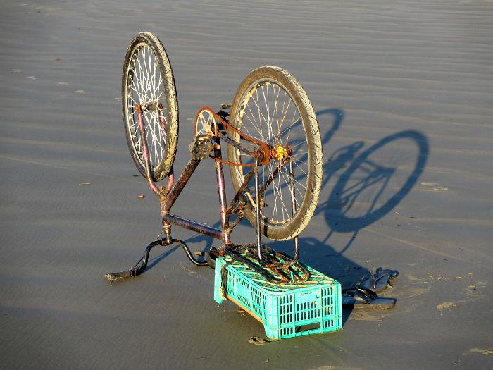 Foto van fiets op zijn kop op strand