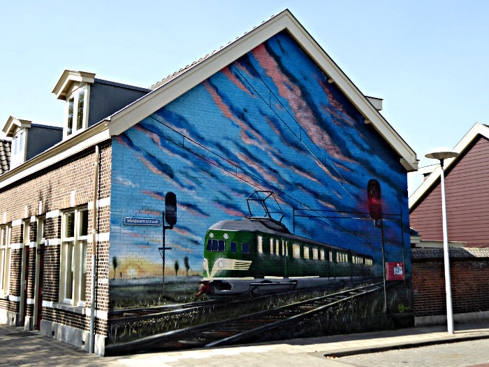 Foto van muurschildering met trein onder avondlucht