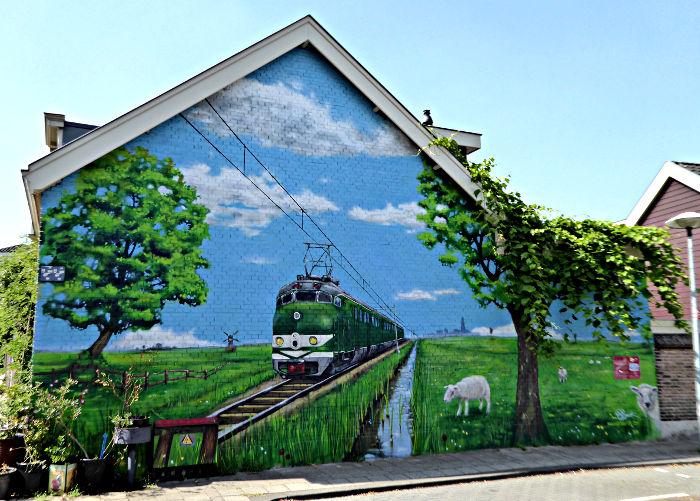 Foto van huis met muurschildering van trein