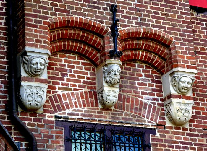 Foto van muur met drie koppen in reliëf