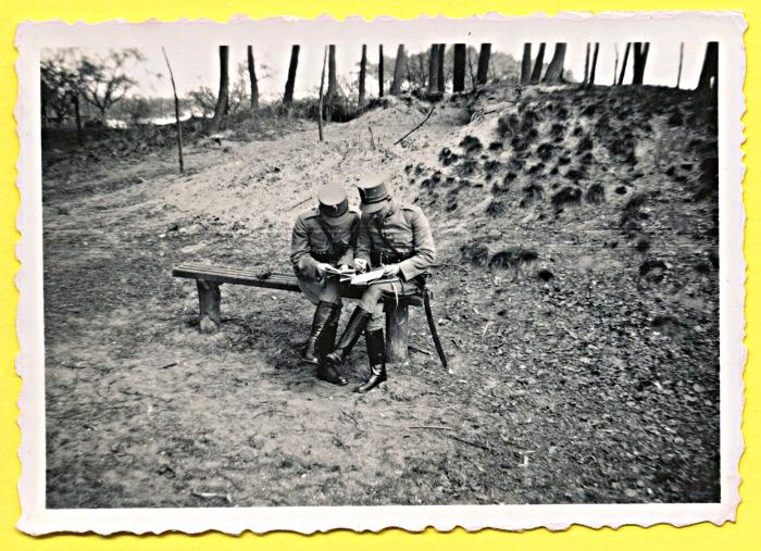 Foto van militairen op bankje in bos kijkend op papieren