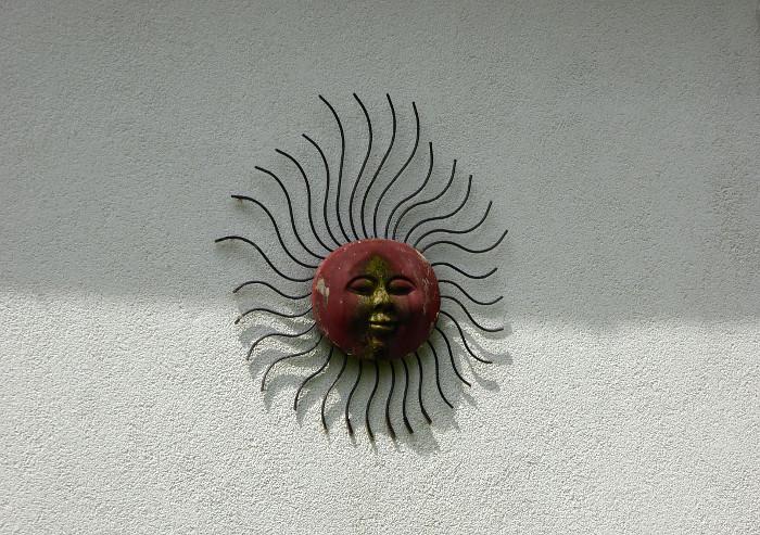 Foto van metalen zon aan muur