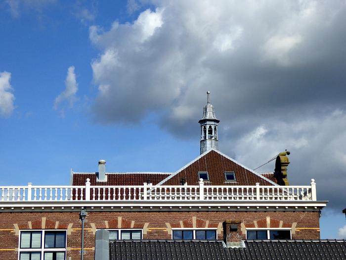 Foto van dak met torentje en wolkenlucht