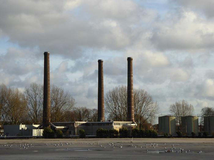 Foto van fabrieksschoorstenen en wolkenlucht